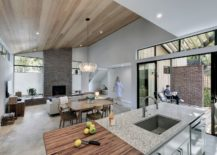 Light-filled-living-area-of-the-house-with-cozy-wooden-ceiling-and-stone-fireplace-217x155