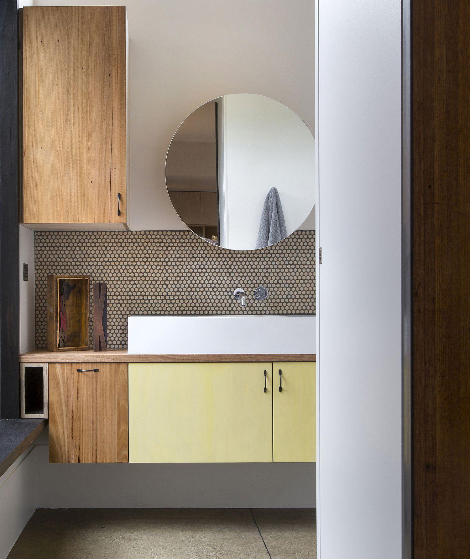 Minimal modern bathroom with round mirror and penny tile backsplash