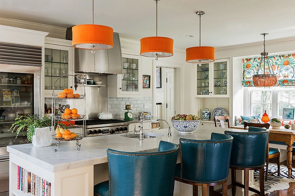 Pendants bring orange to the kitchen while the high and plush bar chairs add blue