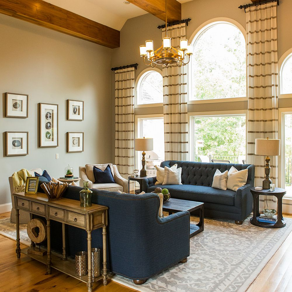 Traditional living room with wooden ceiling beams and bright blue sofas