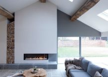 Wooden-logs-stacked-in-the-corner-add-woodsy-element-to-a-minimal-living-space-in-white-with-wooden-ceiling-beams-217x155