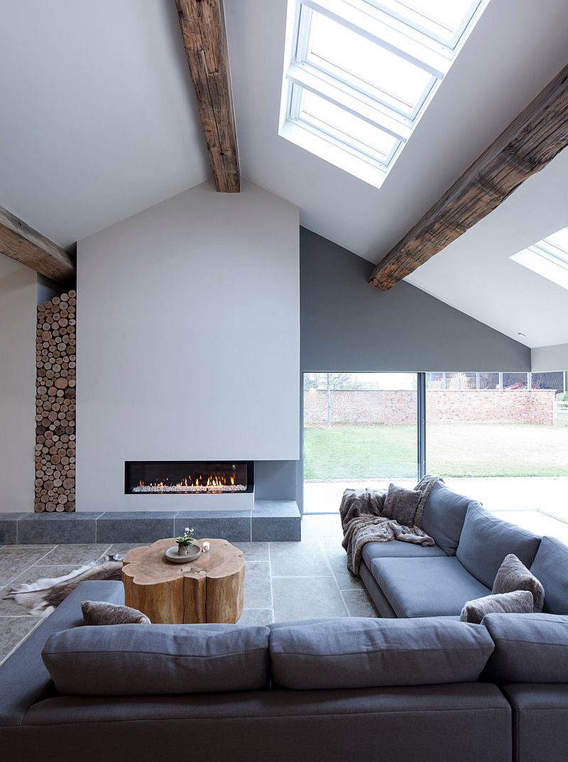 Wooden logs stacked in the corner add woodsy element to a minimal living space in white with wooden ceiling beams