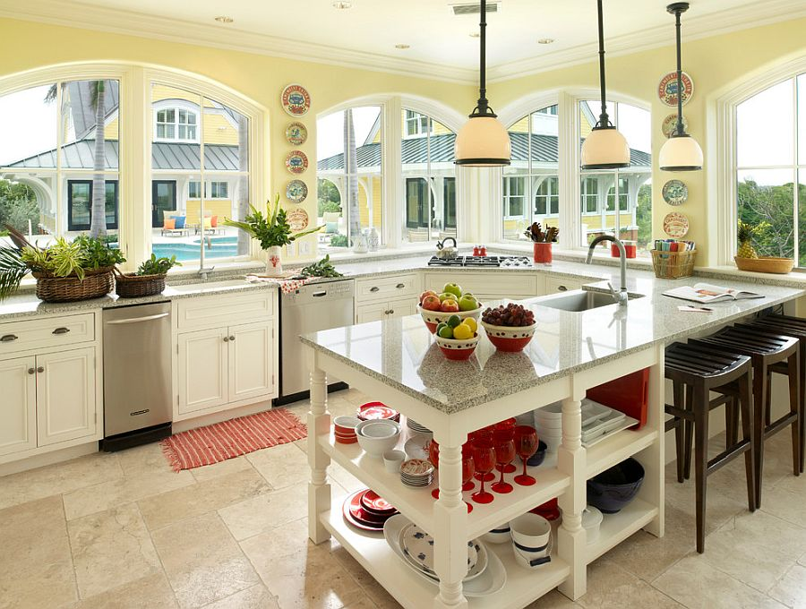 Yellow walls and pops of red give this open, tropical kitchen a cheerful vibe