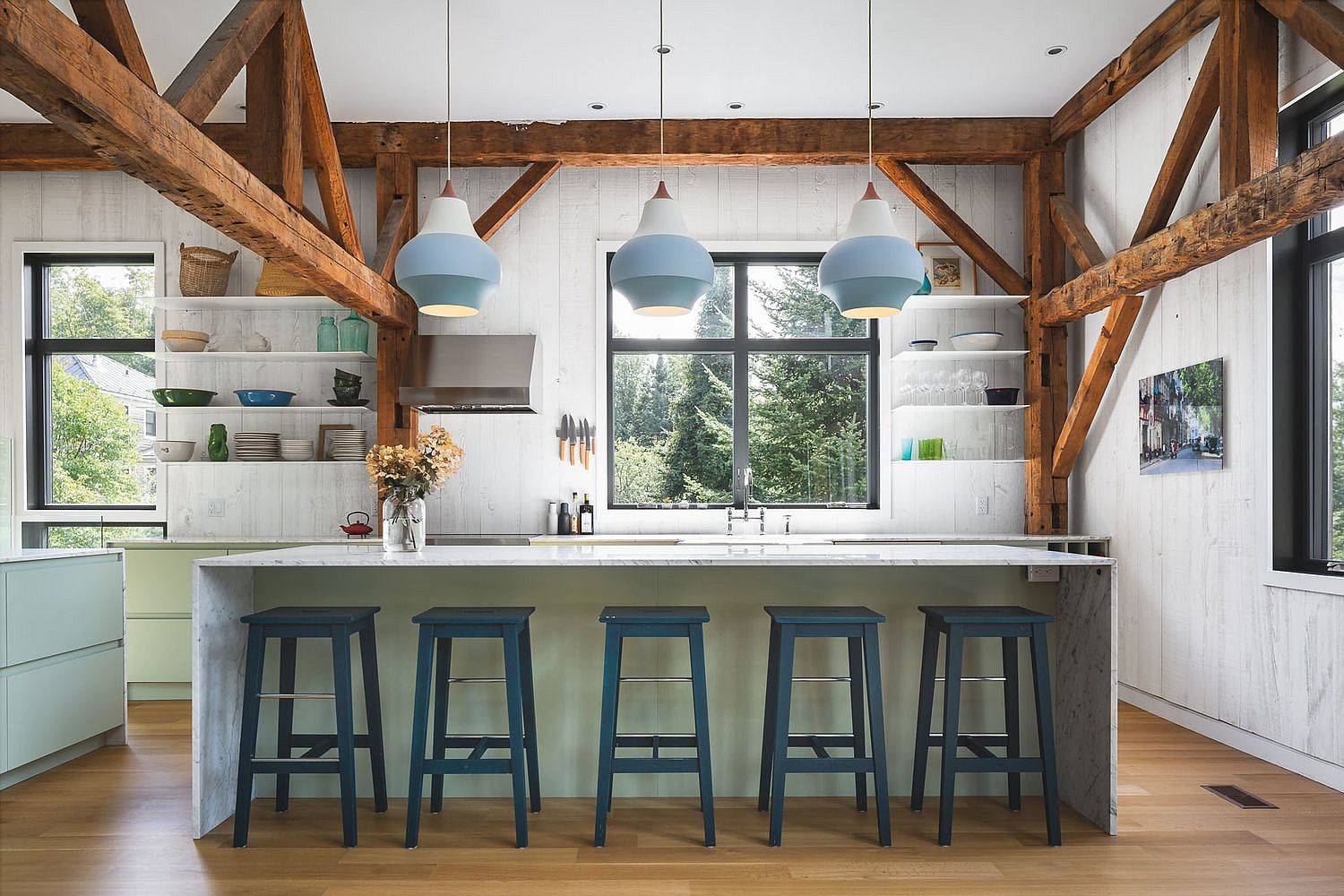 Beautiful farmhouse style kitchen with floating white shelves, light green cabinets and blue pendant lights