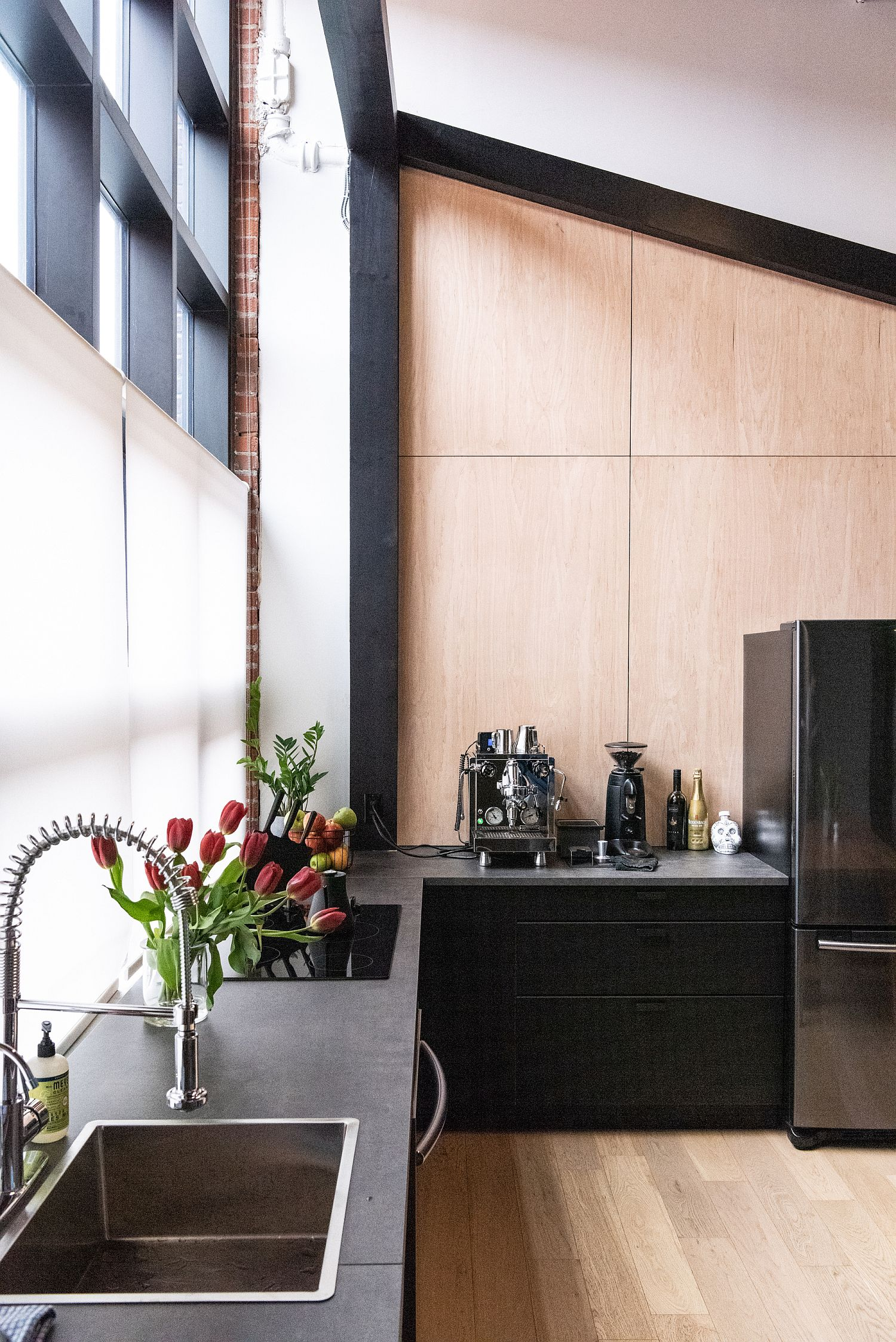 Beautiful wood and black kitchen with ample natural lighting