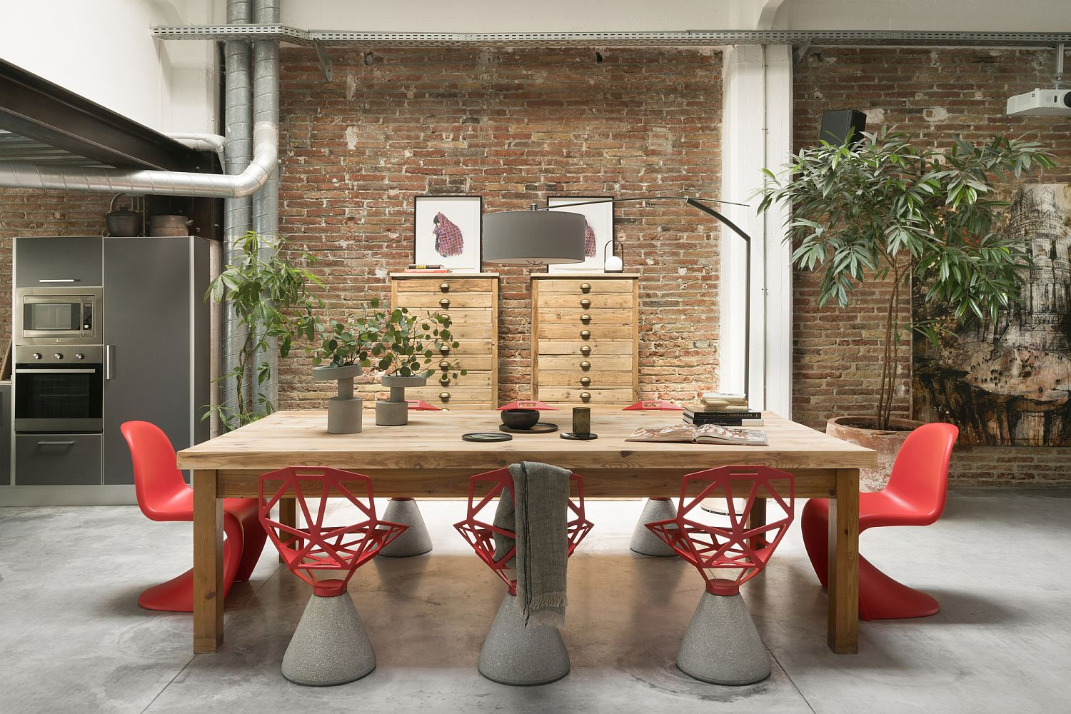 Chairs in red add color to an otherwise neutral dining space with brick wall