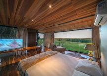 Comfy-bedroom-with-glass-wall-and-smart-decor-217x155