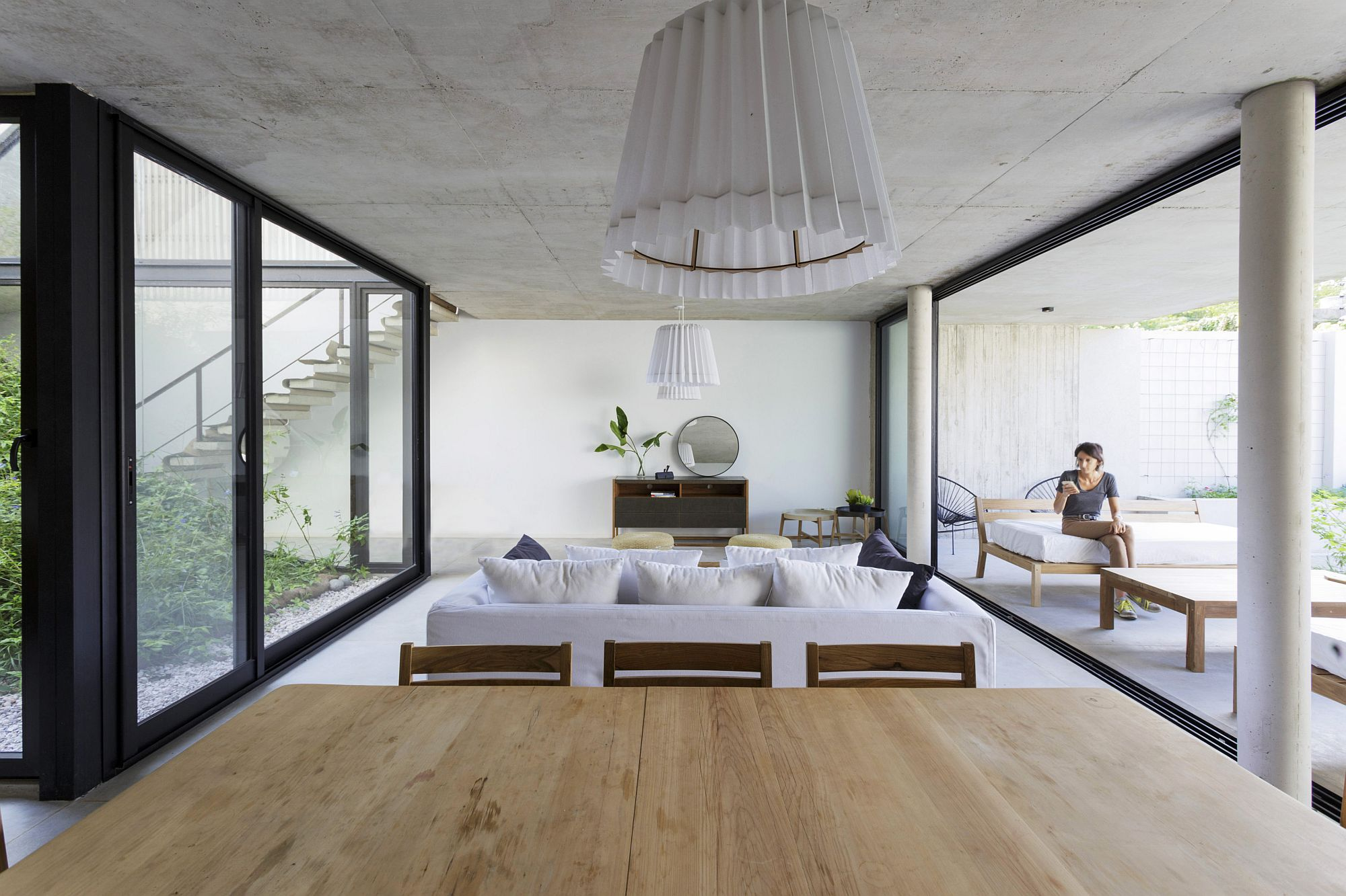 Concrete ceiling brings textural beauty to the living room in white and wood