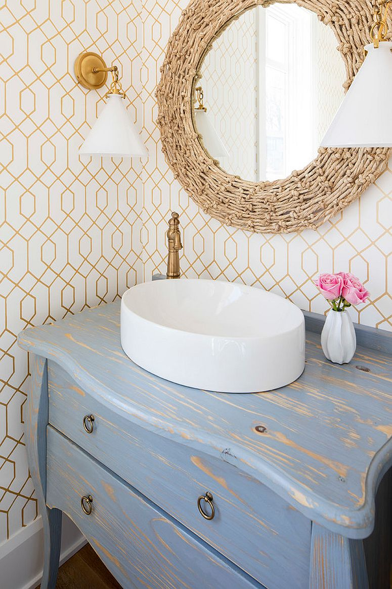 Decor with distressed finishes add to the coastal look of the ultra-tiny powder room