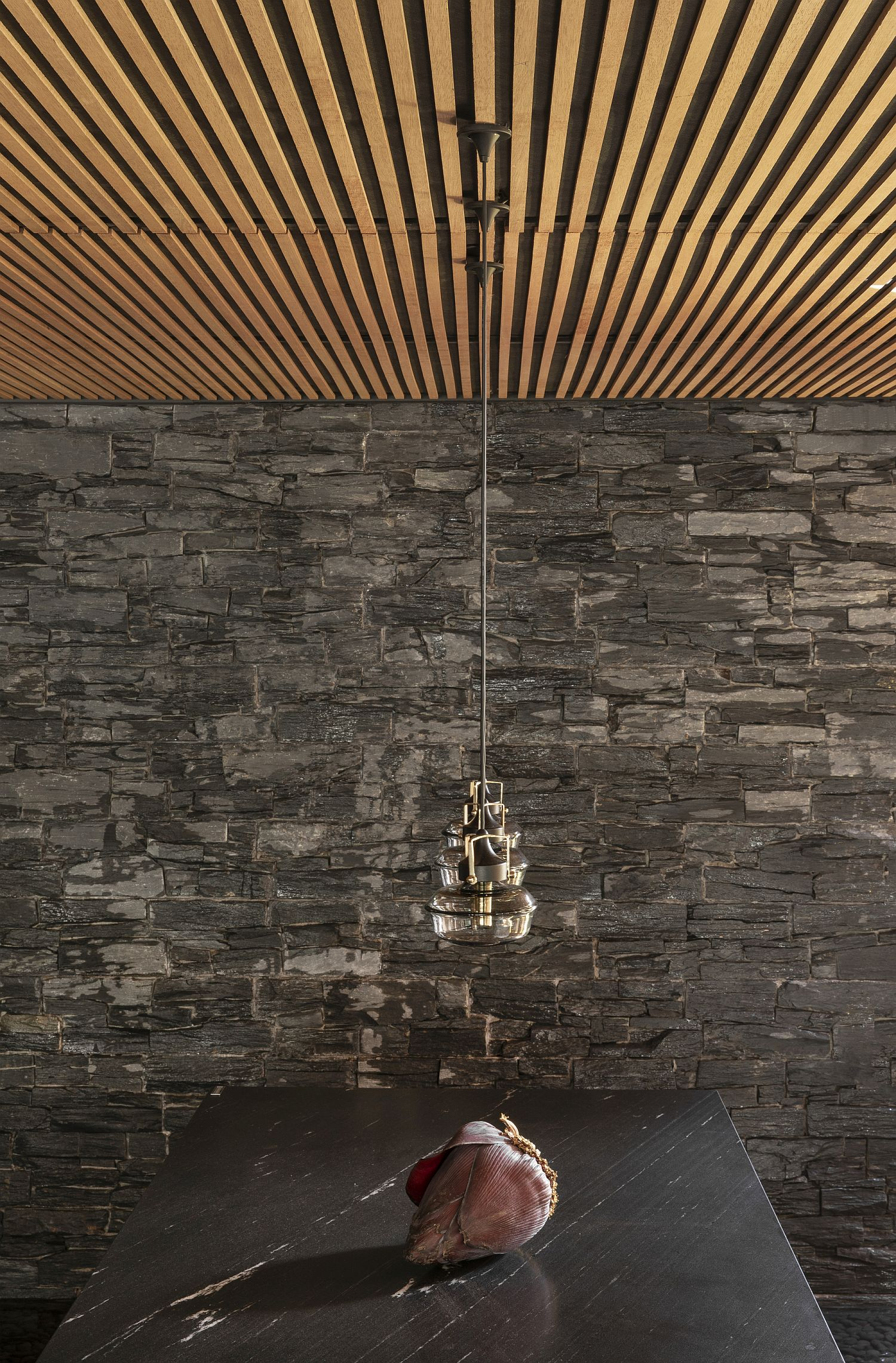 Dining-room-with-wooden-ceiling-and-stone-wall-backdrop