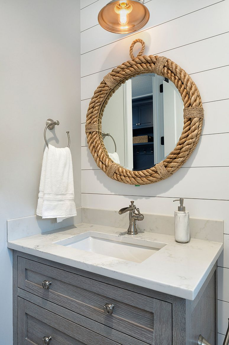 Mirror with rope frame accentuates the coastal appeal in this white powder room