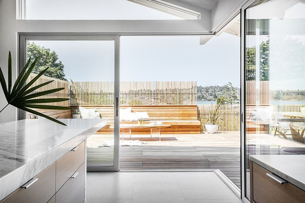 Multi-sliding-doors-with-aluminum-frames-connect-the-kitchen-and-dining-space-with-deck-outside