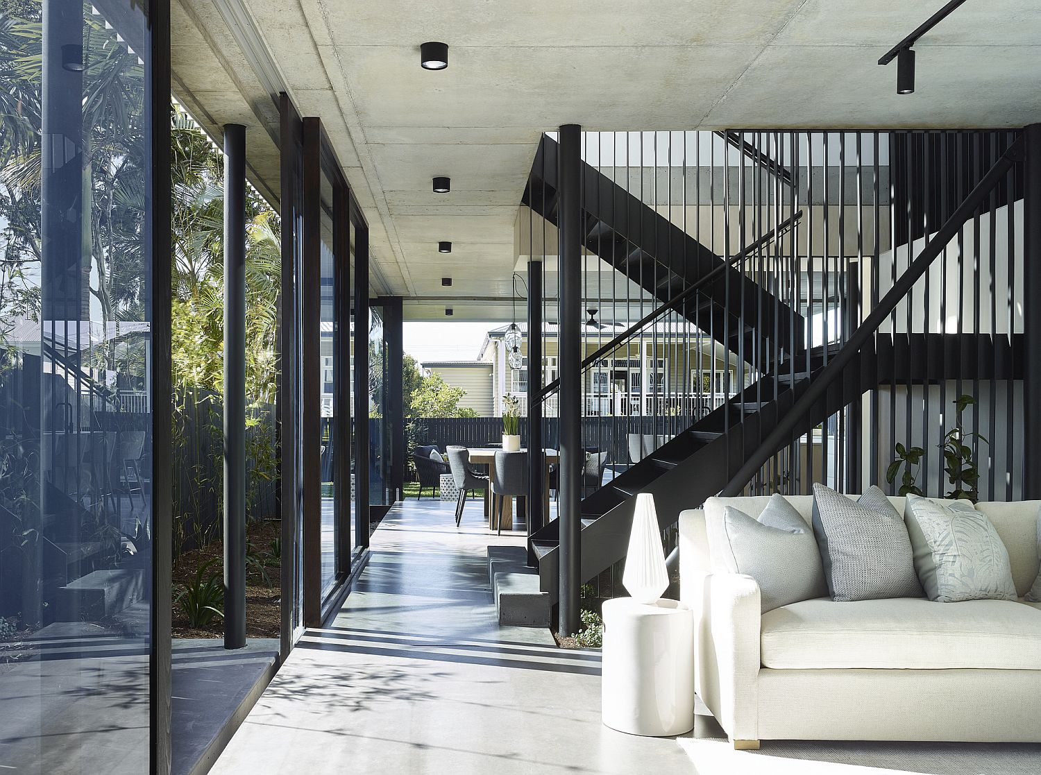 Open plan living area of the house in white with glass walls
