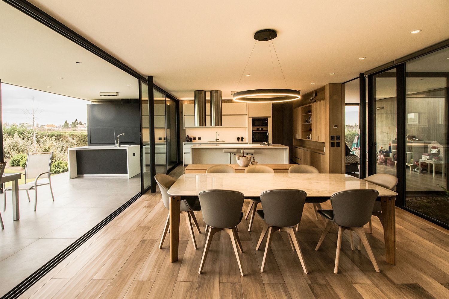 Open plan living area of the housewith outdoor kitchen and dining next to it