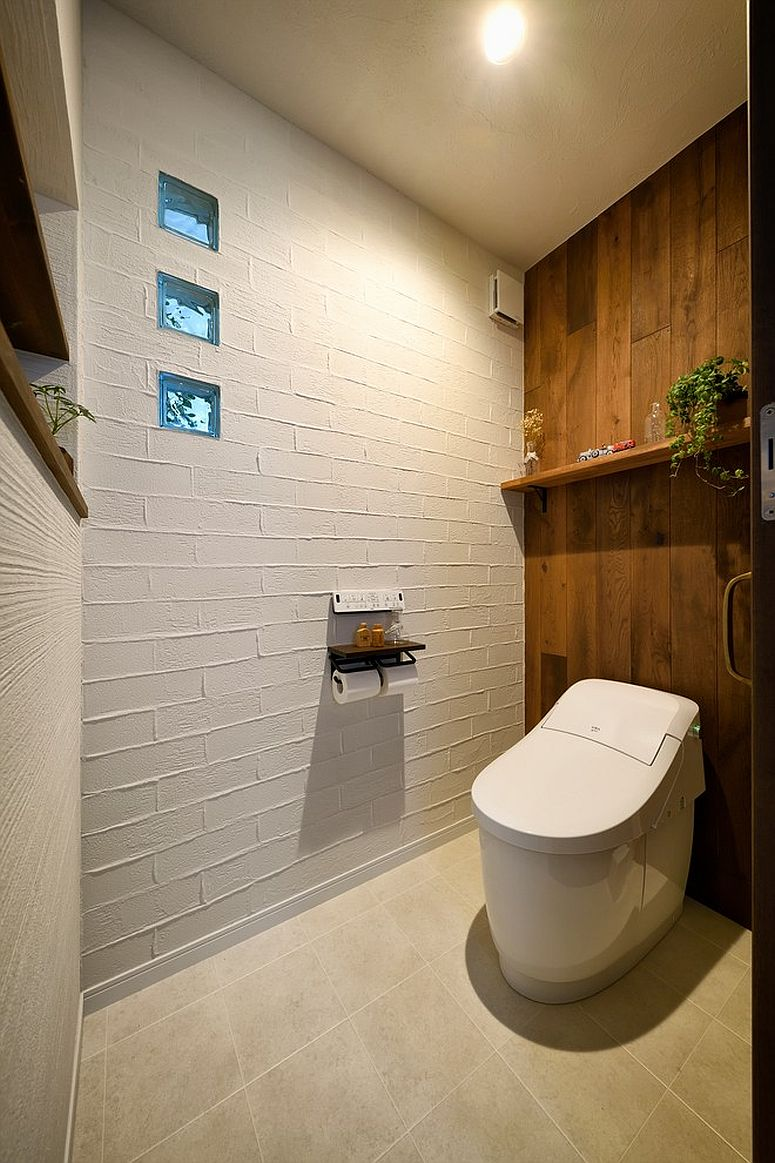 Painted brick wall and wood wall coupled in style inside the small powder room