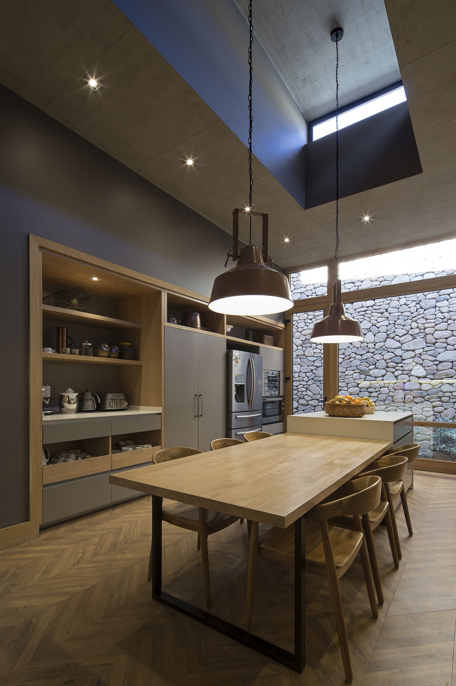 Pendant lights hanging from the double-height dining area and kitchen