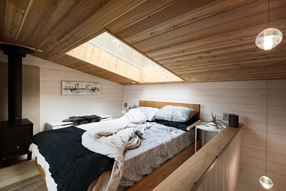 Skylight above the bedroom bed offers a window into the sky