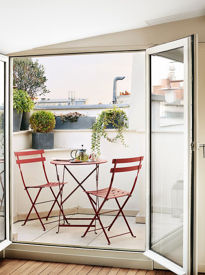 Slim chairs and table bring a dash of red to this tiny balcony in Paris apartment