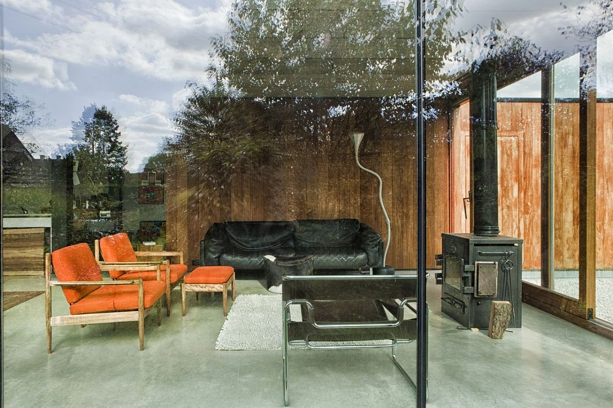Small-and-simple-living-area-with-glass-walls-and-comfy-decor