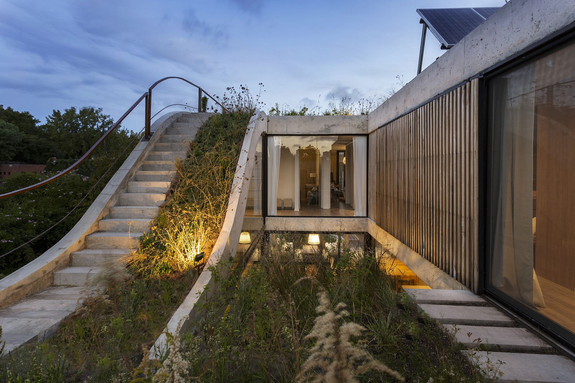 System of green ramps connects different levels of the house and adds ample greenery