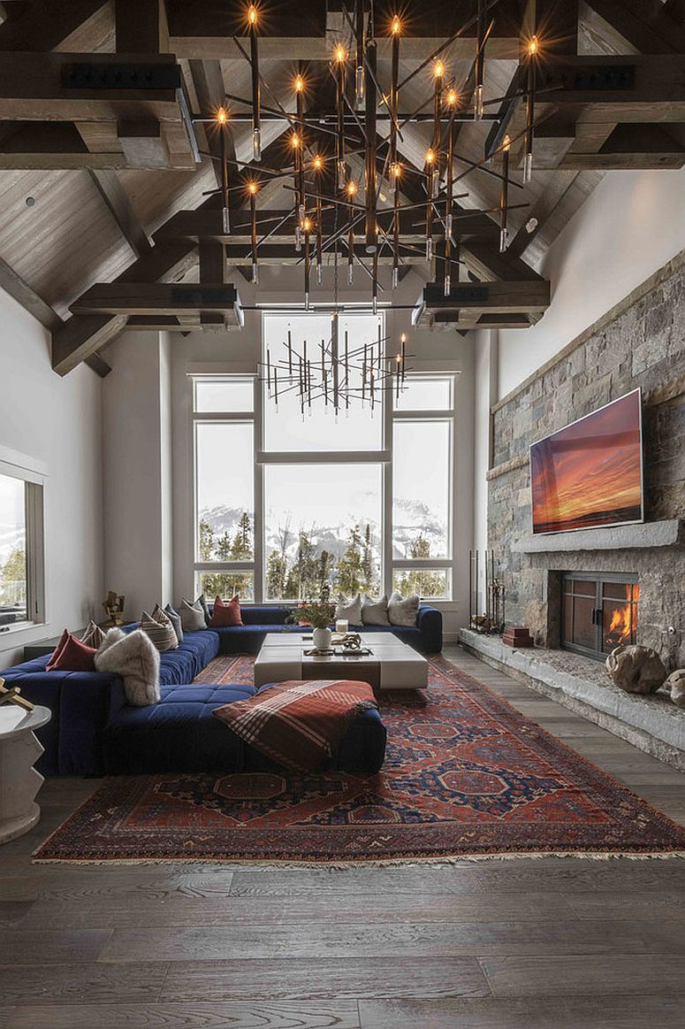 Vaulted ceiling, brilliant chandelier and wooden accent wall shape this spacious living room