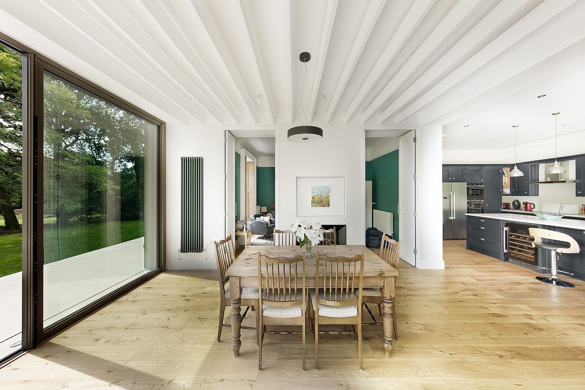 White-and-wood-dining-area-of-the-house-with-sliding-glass-doors-connecting-it-to-the-deck-outside