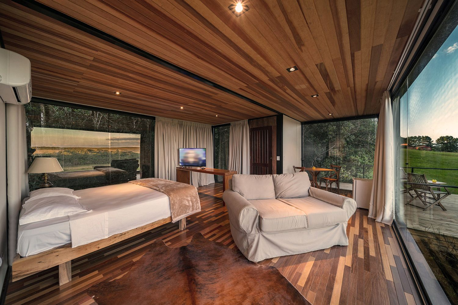 Wood and glass bedroom of the cabin with wonderful view of the landscape around it