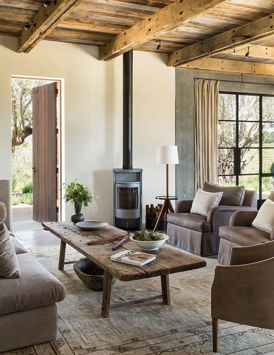 Wooden coffee table, ceiling beams and fireplace add rustic beauty to the living room