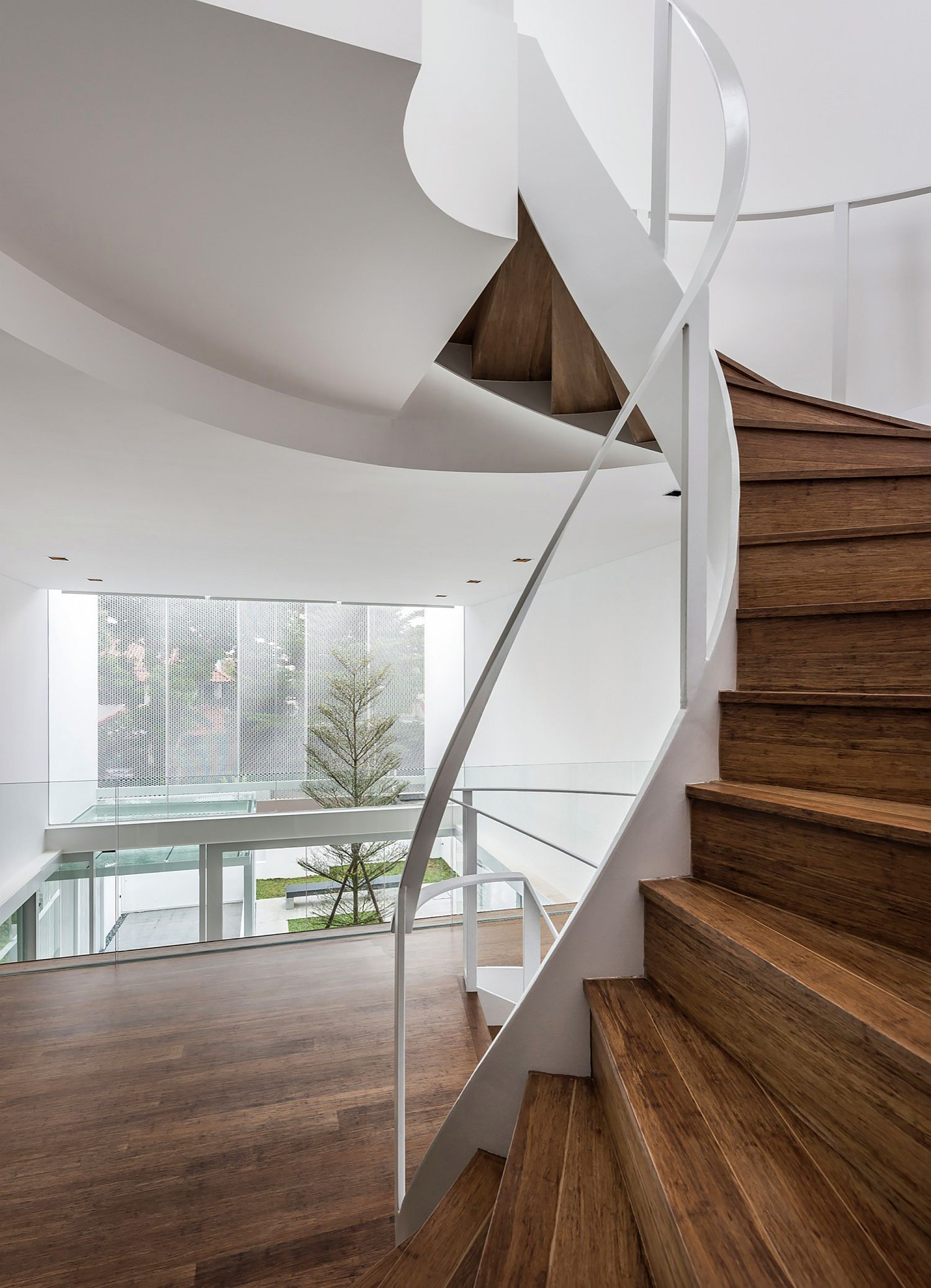 Awesome contemporary wooden staircase is the central focal point of the house