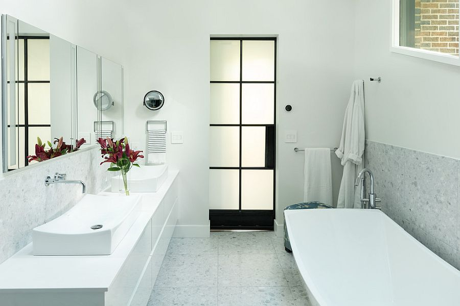 Black of the door anchors the white bathroom and defines it beautifully
