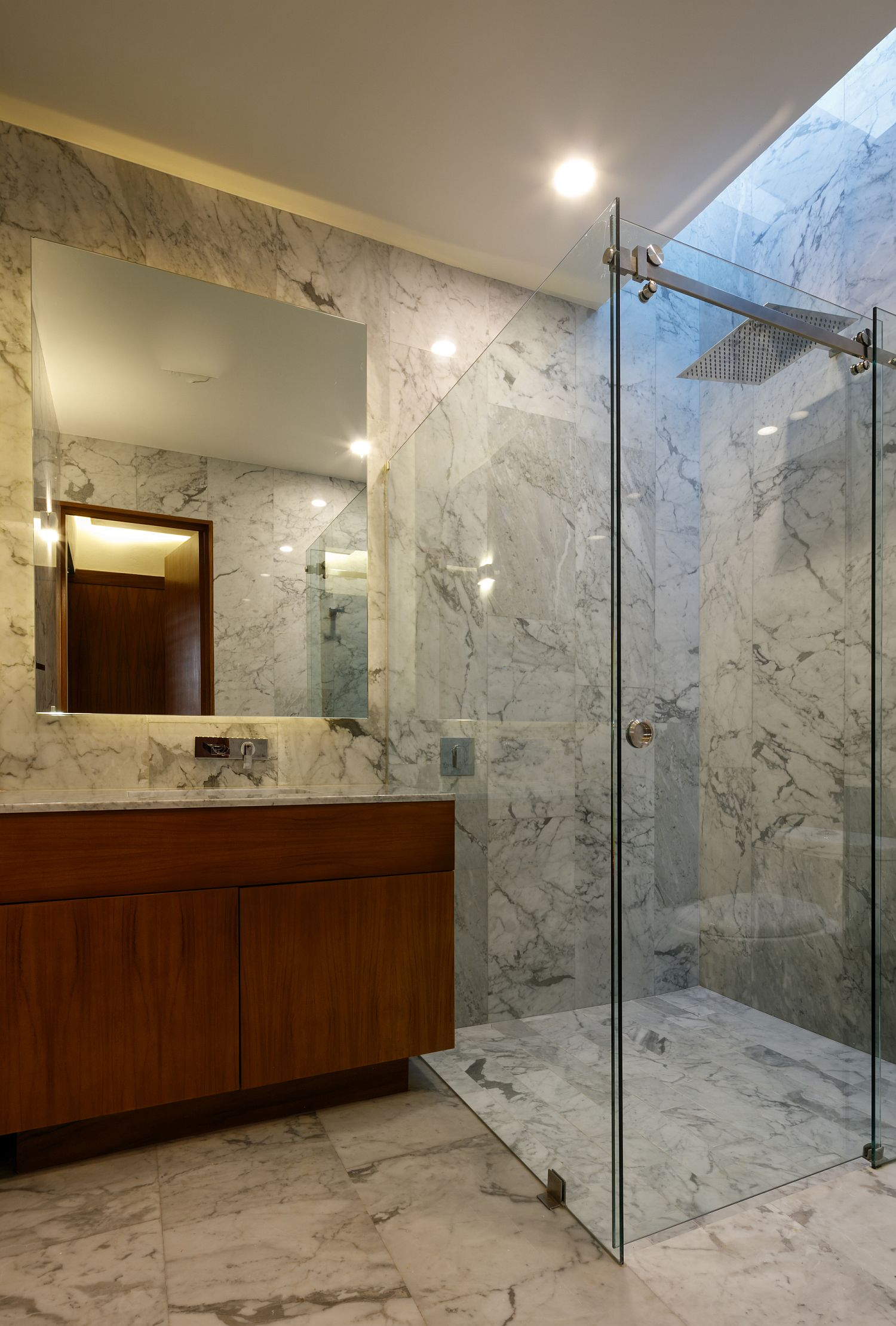 Contemporary bathroom in stone with corner glass shower area