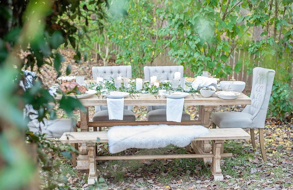 Dreamy outdoor dining surrounded by greenery and gorgeous candle lighting