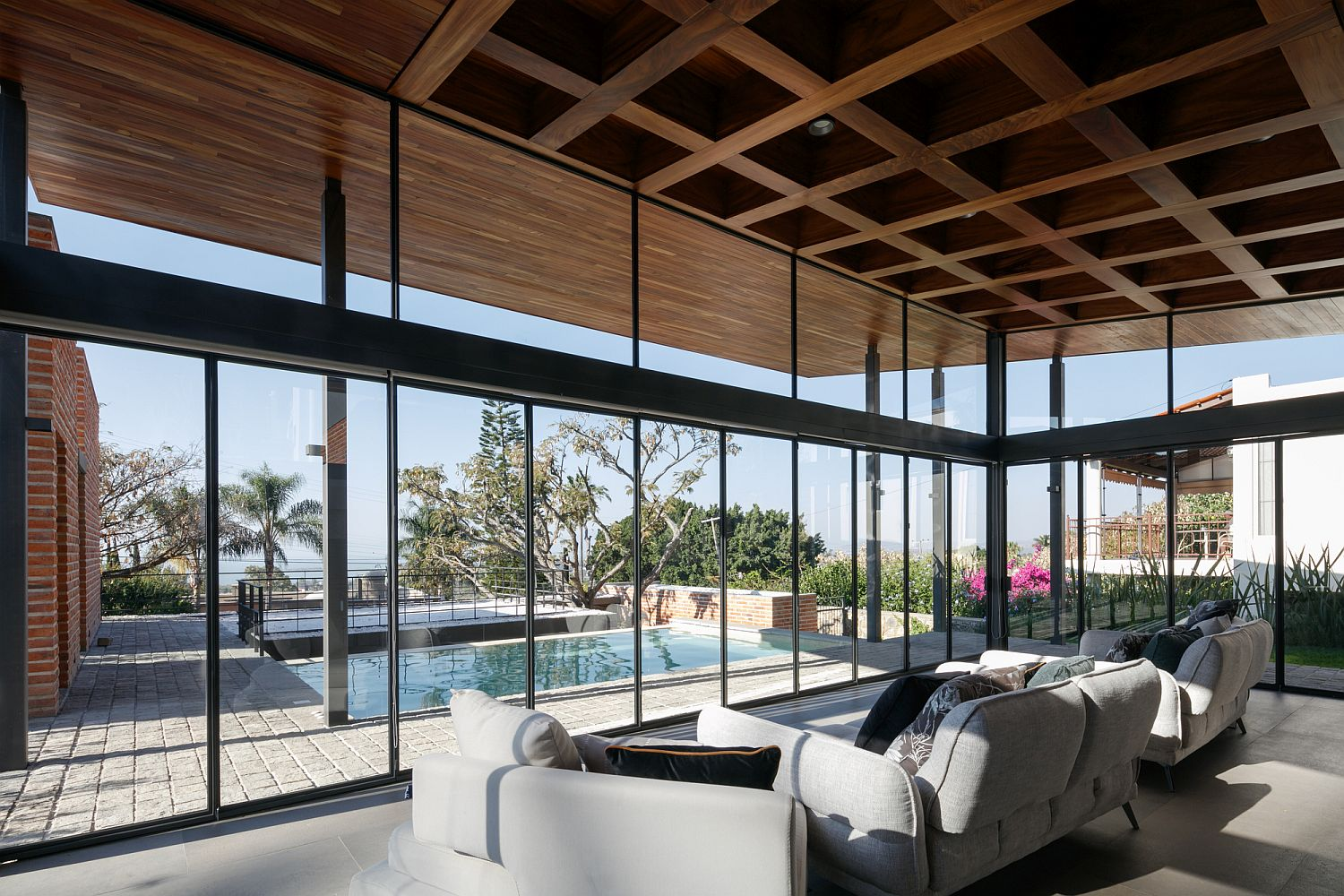 Glass walls and sliding glass doors connect the interior with the pool area