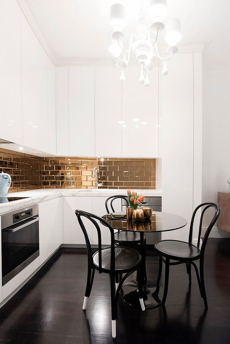 Gold mirrored backsplash coupled with chandelier in the tiny white modern kitchen