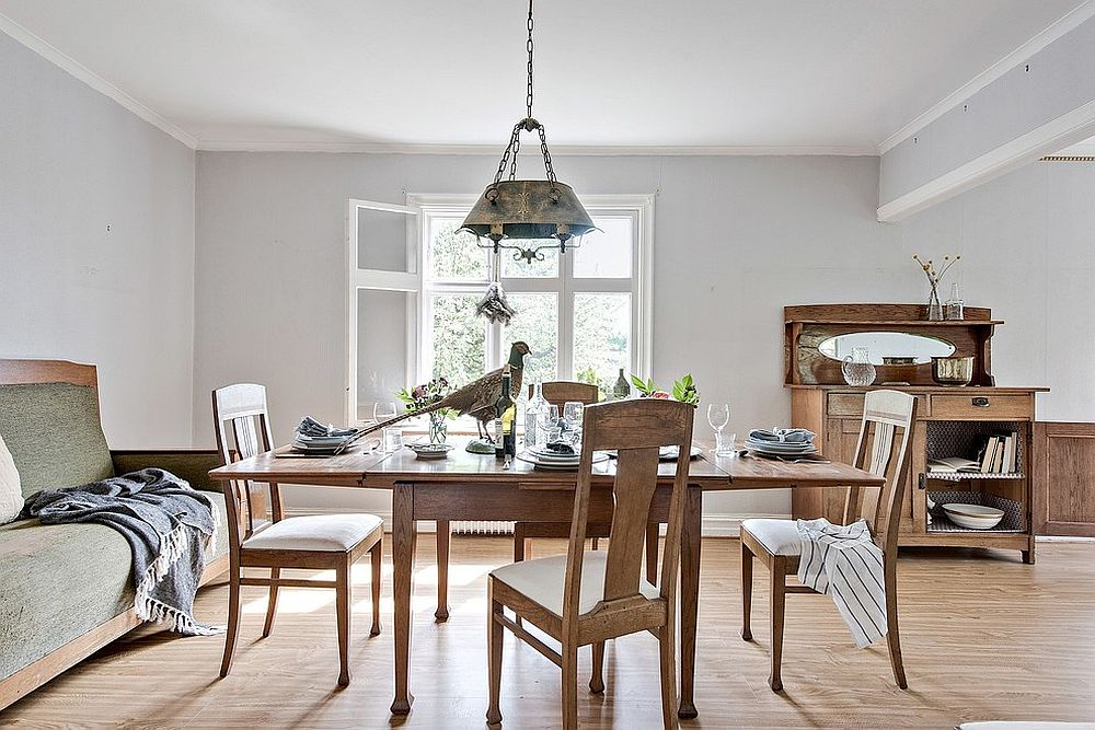 Large window brings ample natural light into the wood and white dining room