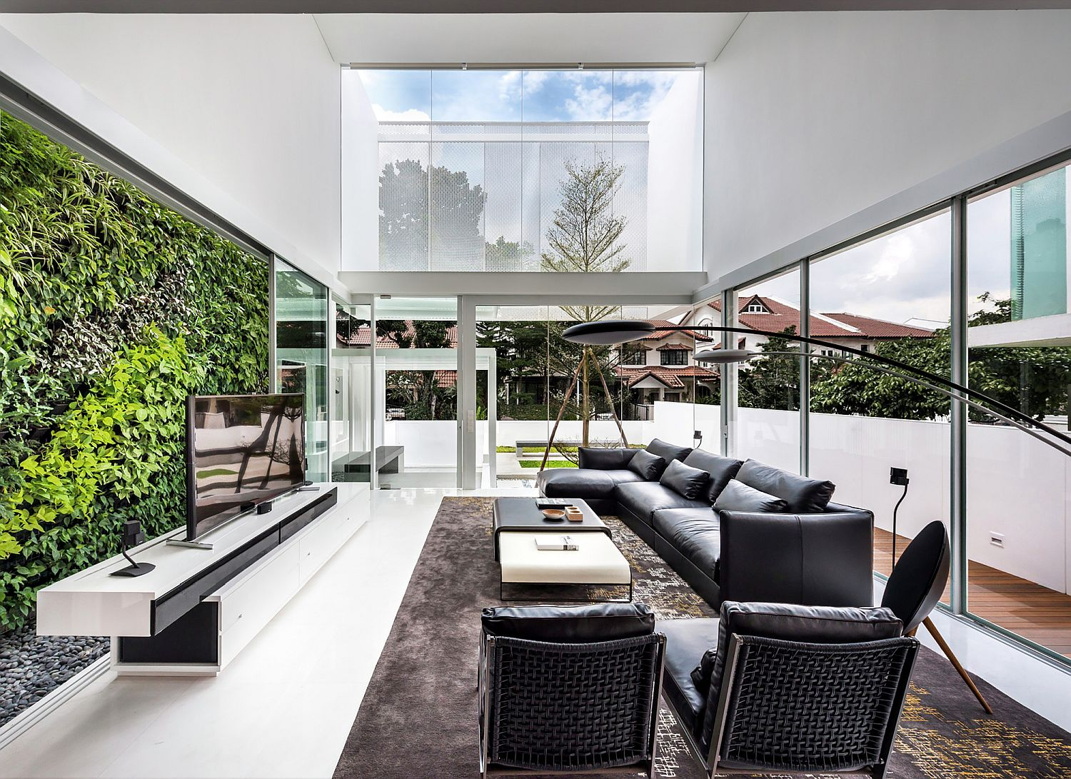 Living room with green wall in the backdrop and ample natural light