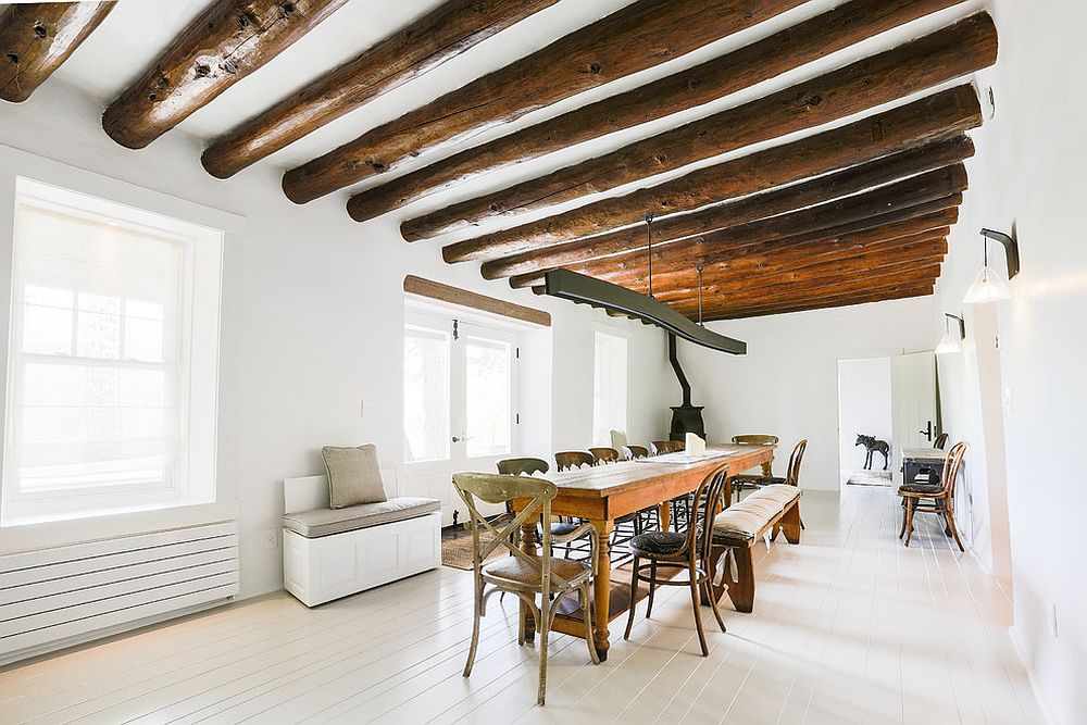 Majestic white and wood dining room with ceiling beams that bring coziness