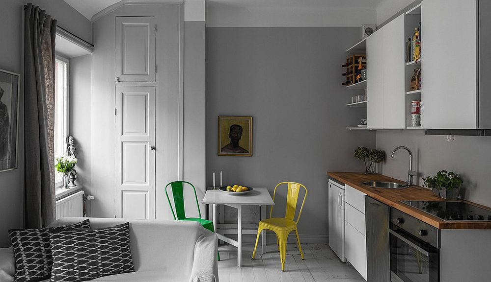 Monochromatic kitchen with colorful chairs for the breakfast zone