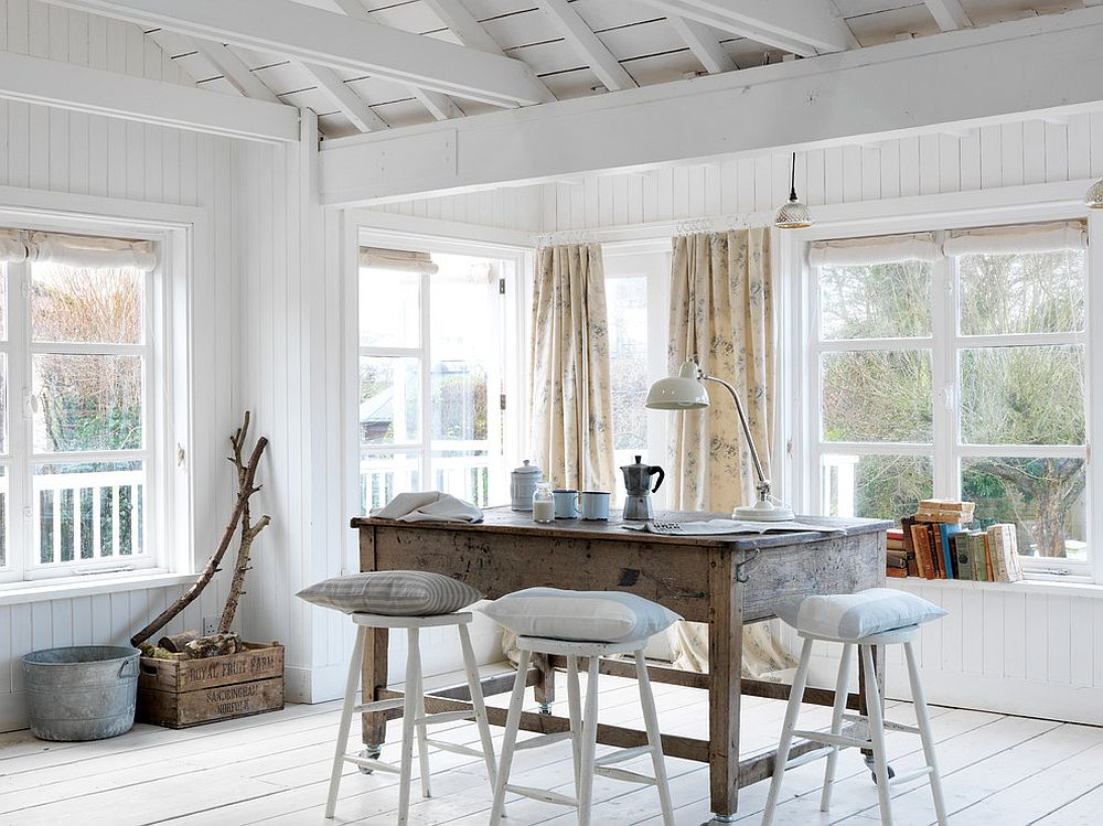 Natural wood table and white backdrop for the coastal dining space