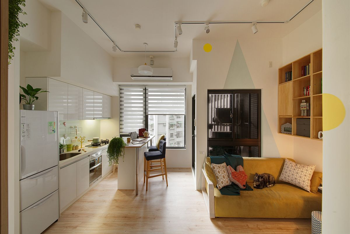 Track lighting is used to illuminate the kitchen along with the living space next to it