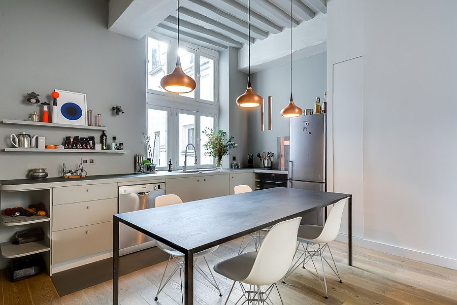 Trio of copper pendants along with the window lights up the modets kitchen