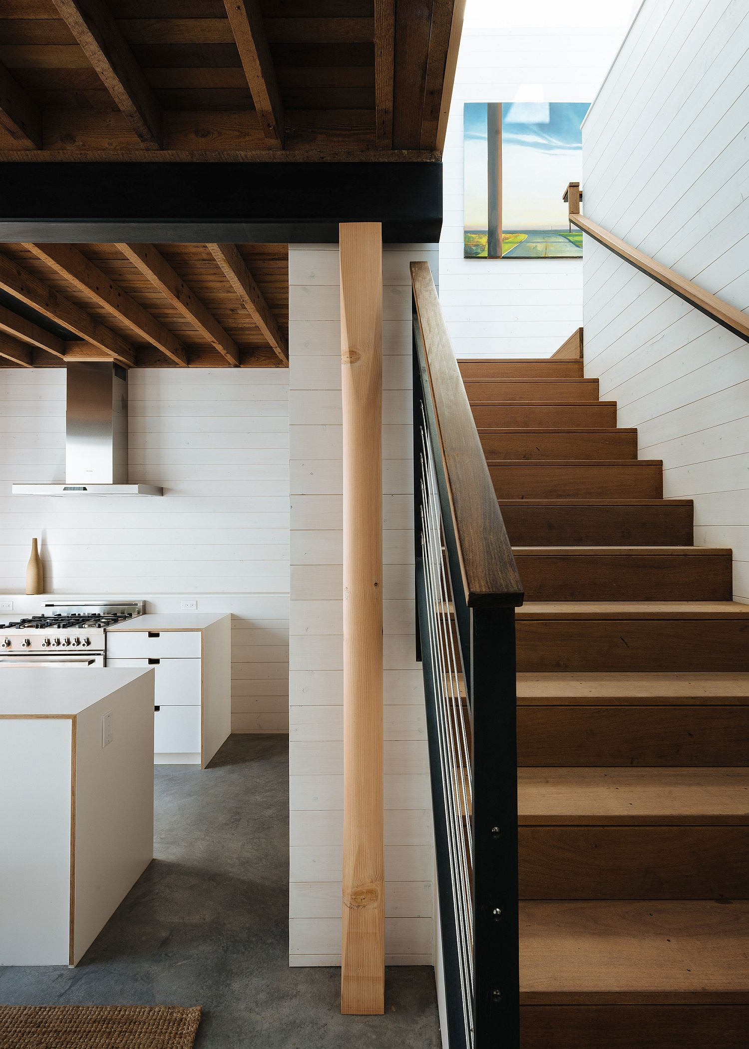 Wood, white and natural light shape the interior of the transformed house