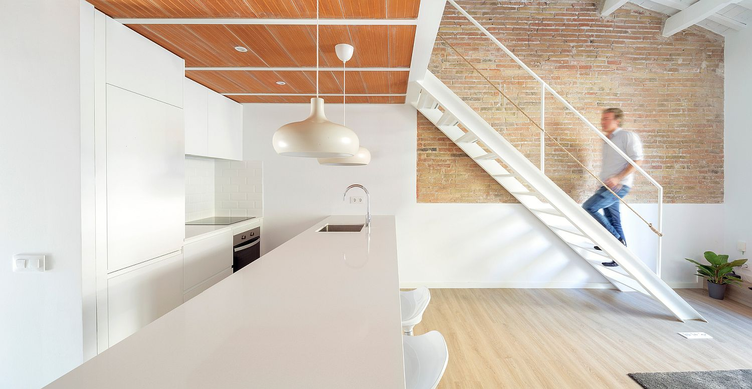 All-white kitchen under the mezzanine level with wooden ceiling above