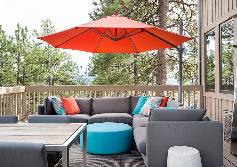 Giant umbrella in orange and accent pillows in orange and blue bring color to the gray outdoor couch