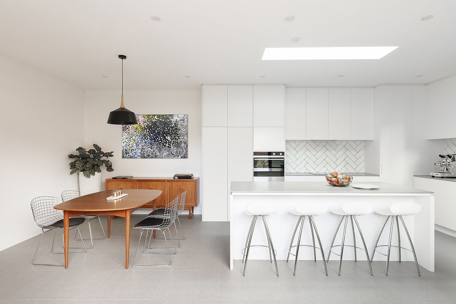 Gorgeous kitchen in white with wooden dining table that stands out visually
