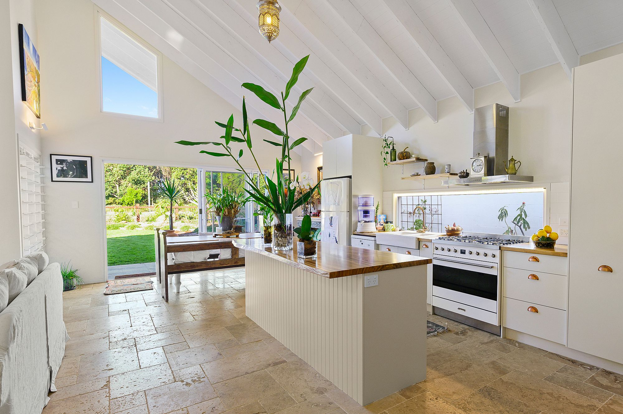 Subtle-use-of-green-and-yellow-in-the-white-kitchen-with-ample-natural-light