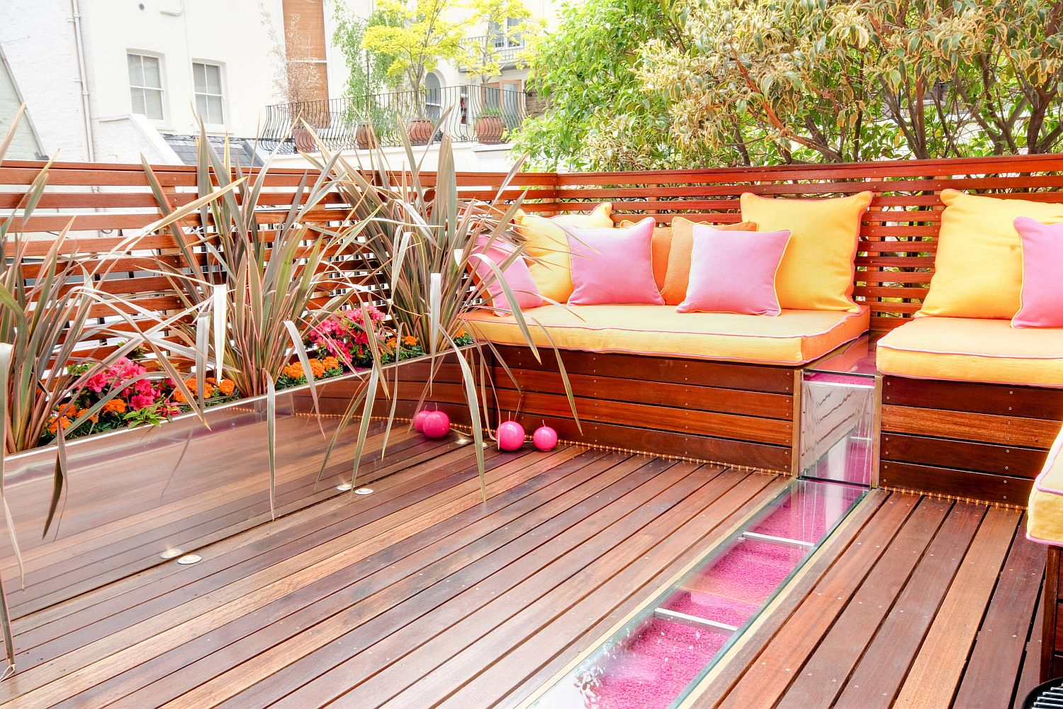 Throw pillows bring pink ad orange to the outdoor deck