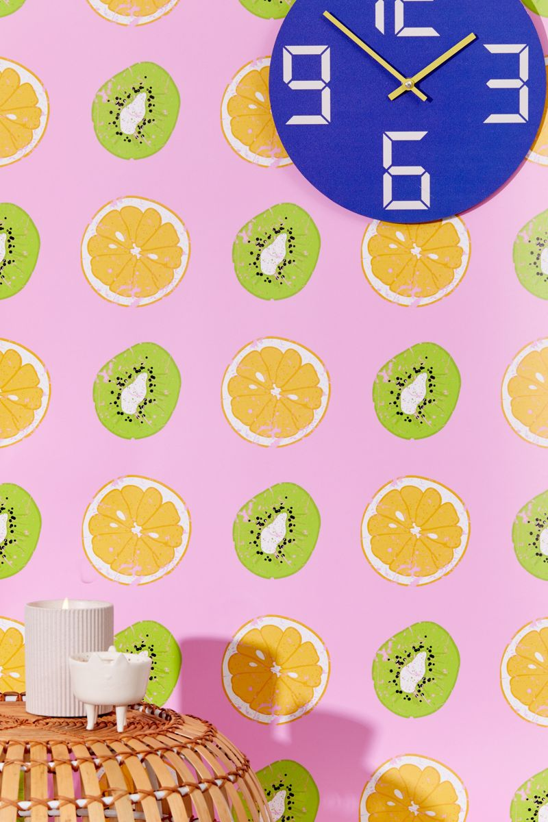 bright and bold pink wallpaper with large oranges and kiwis