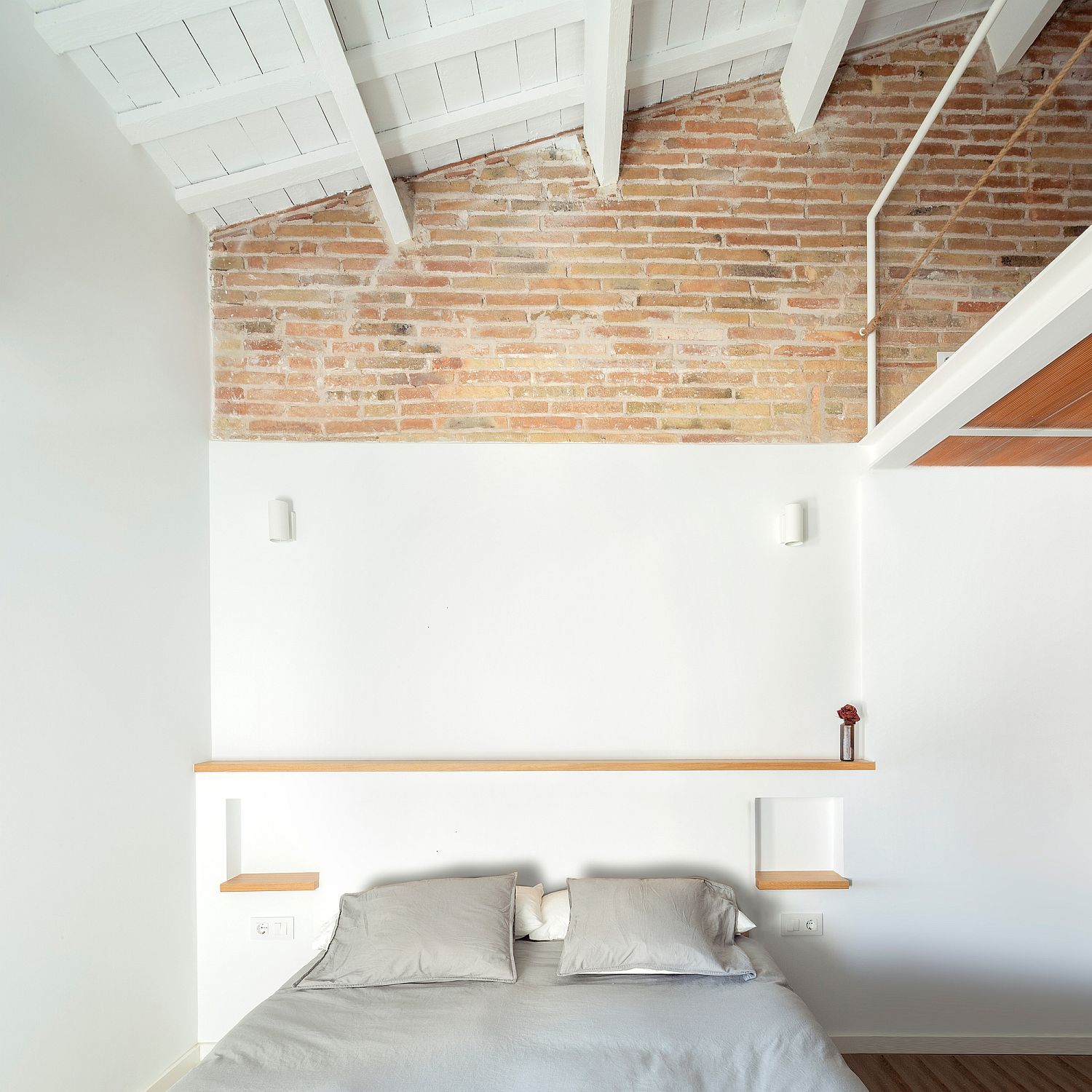 Wall painted in white along with ceiling beams and brick wall section for the small bedroom