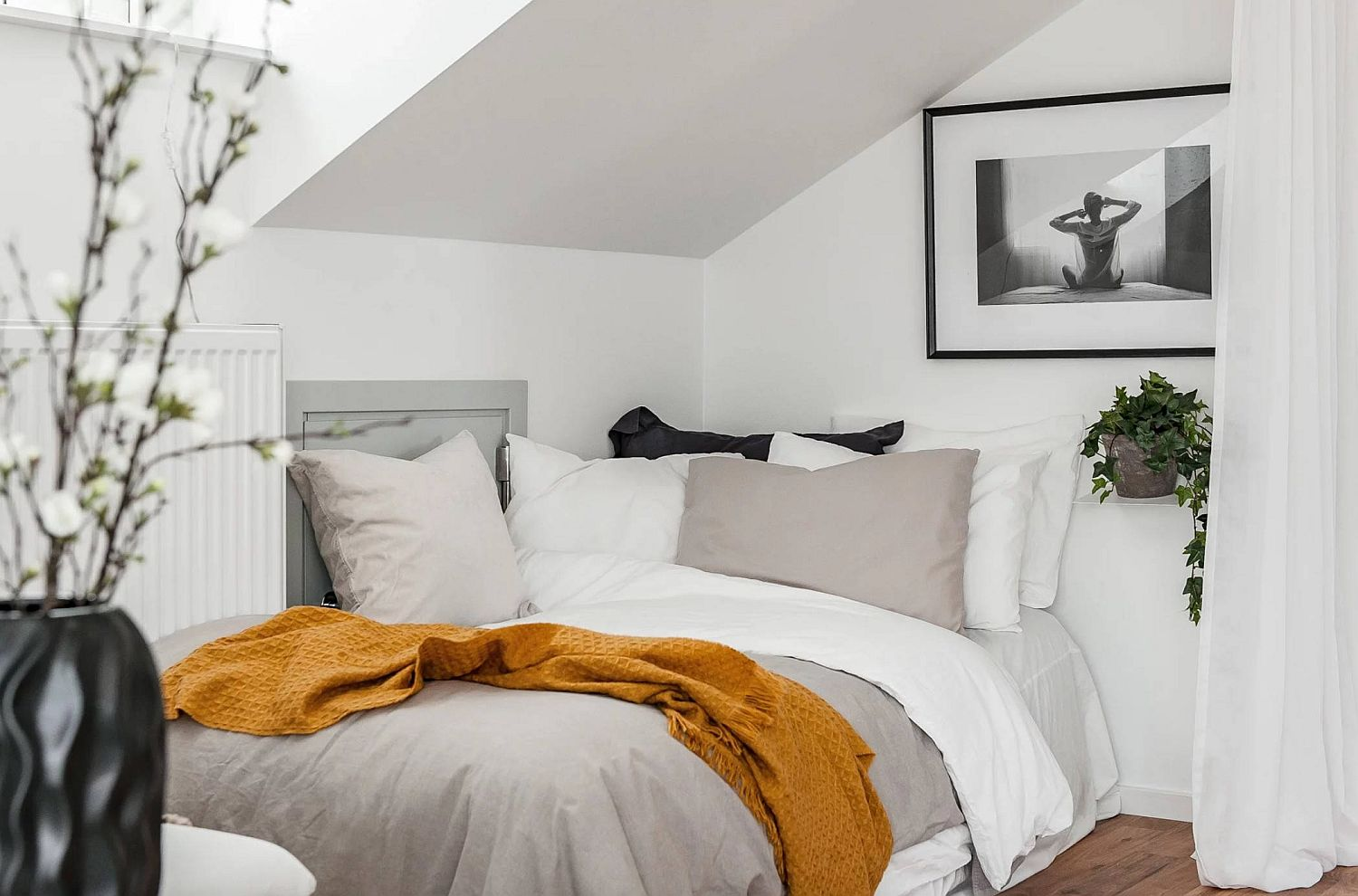 Bed in the corner and drapes save space in the small bedroom